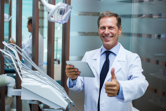 Your results are perfect. Cheerful dentist looking at camera with smile and gesturing thumb up while standing in dentist's office