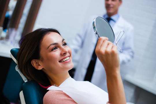 Now my smile is perfect! Beautiful young woman looking at mirror with smile in dentist's office