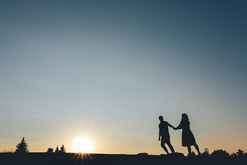 Silhouette of couples who holding hands climbs the hill