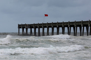 A red flag, warning of dangerous conditions, is seen on a pier in advance of Hurricane Michael in Pensacola