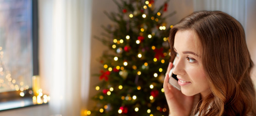 technology, communication and holidays concept - happy young woman calling on smartphone at home over christmas tree lights background