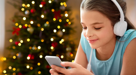 children, technology and people concept - close up of happy girl with smartphone and headphones listening to music over christmas tree lights background