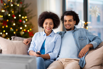 people, family and leisure concept - happy african american couple watching tv at home over christmas tree lights background