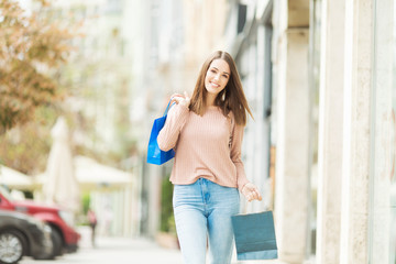 Young woman with shopping bags on the street smiling