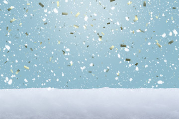 FALLING SNOW FLAKE WITH GOLDEN SHINY CONFETTI FROM BRIGHT BLUE SKYS WITH WHITE SNOW ON THE GROUND