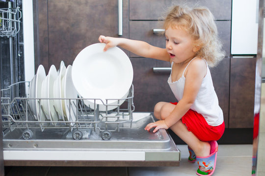 Cute blonde toddler girl helping in the kitchen taking plates out of dish washing machine