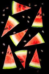 Watermelon slices cut into triangles, watermelon bones. Black background.