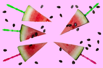 Watermelon slices cut into triangles on sticks, watermelon bones. Pink background.