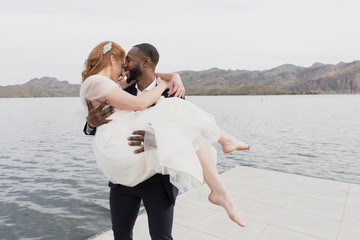 Happy loving husband carrying wife while standing on pier over lake