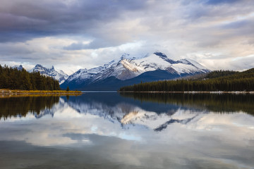 Scenic view of Maligne lake by snowcapped mountain against cloudy sky at Jasper National Park during sunset
