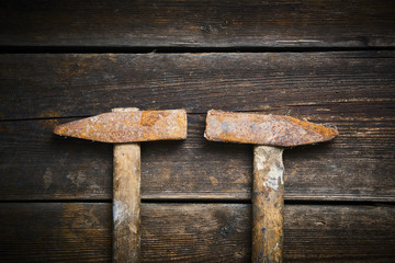 Close up of two old used hammer on a rustic wooden background. Selective focus