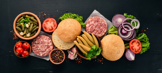Preparation of burger. Meat, fresh vegetables, tomatoes, onions. On a black wooden background. Top view. Free copy space.