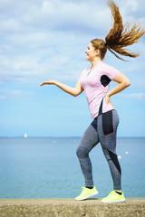 Woman exercising next to sea