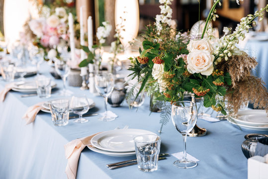 Festive table decorated with flowers and candles on a silver candlestick on blue tablecloth