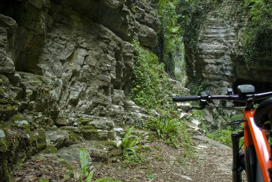 "electric bike, e-bike, ebike, mtb, mountain, rock canyon created by a river, forest, summer, sport, adventure, freedom, alps, Path called ""Strada della Forra"", Garda Lake, Lombardy, Italy"