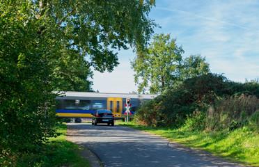 Bahnübergang mit wartendem Auto und vorbeifahrendem Zug. Standort: Deutschland, Nordrhein-Westfalen, Marbeck