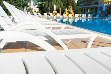 Beach chairs side swimming pool close-up