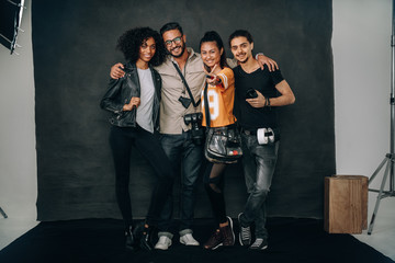 Studio shot of photographer standing with his crew