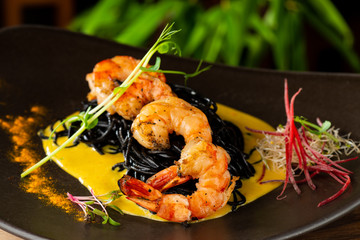 "Thai fine dining/ Fresh cilantro marinated ""Black Tiger"" shrimps and mango sauce on black noodles"