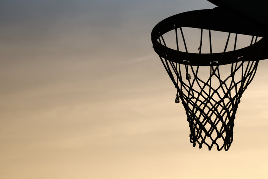 Basketball hoop silhouette in the sunset. cirrostratus clouds background