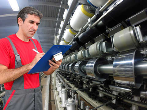 Quality Control in Textile Industry / Quality control inspector using clipboard and writing in modern textile mill