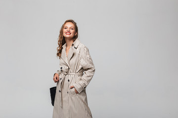 Young pretty cheerful woman with wavy hair in striped coat happily looking in camera over gray background isolated