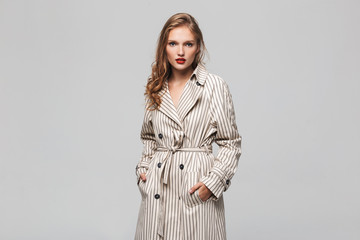 Young beautiful woman with wavy hair in striped coat holding hands in pockets thoughtfully looking in camera over gray background isolated