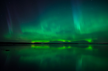 Northern lights dancing over calm lake in Farnebofjarden national park in Sweden