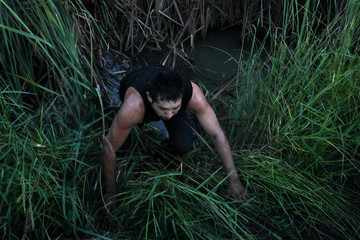 A man from Mexico crawls out of tall grass after he was apprehended for illegally crossing into the U.S. from Mexico in Penitas, Texas