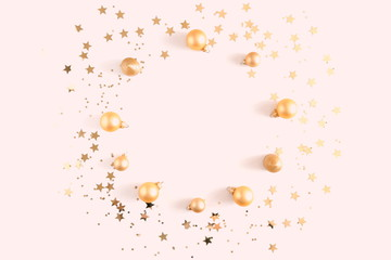 Christmas composition. Xmas wreath of gold decorations on pastel pink background. Flat lay, top view, copy space