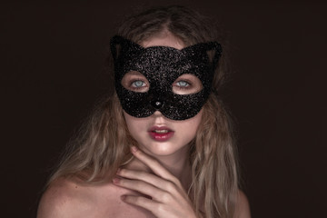 Beautiful young tender woman posing isolated over dark beige chocolate brown background wall wearing carnival cat masquerade mask looking camera.