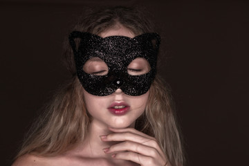 Beautiful young tender woman posing isolated over dark beige chocolate brown background wall wearing carnival cat masquerade mask eyes closed.