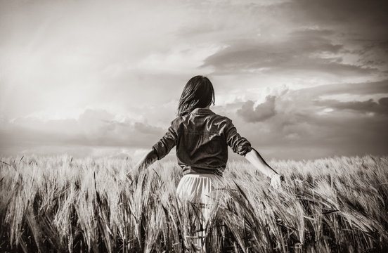 photo of young beautiful woman standing in the field. Image in black and white color style