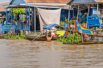 Floating village and a boy swimming in the Tonle Sap Lake in Cambodia