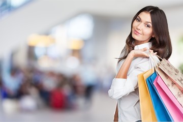 Young woman with shopping bags on  background