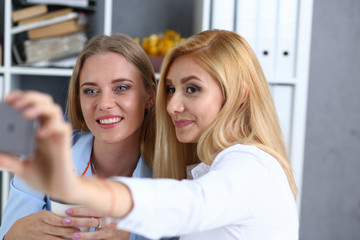 Two businesswomen in the office smile and do selfie