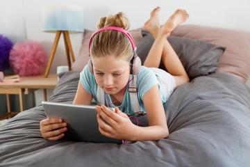 Cute girl using digital tablet in her bedroom