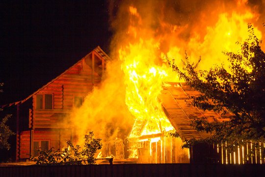 Burning wooden house at night. Bright orange flames and dense smoke from under the tiled roof on dark sky, trees silhouettes and residential neighbor cottage background. Disaster and danger concept.