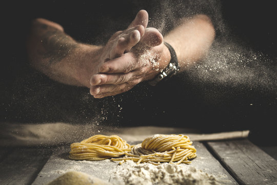 A man claps his hands and sprinkles flour on fresh pasta. Black background, rustic style