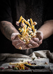 close hand make pasta and throw on a black background before cooking the dish