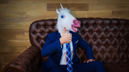 Funny unicorn in elegant suit sits on sofa like a boss and showing gesture thumbs up. Portrait of unusual man at home. Freaky young manager in comical mask.