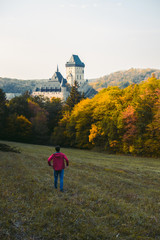 Wall Murals Nepal Man in red jacket looking at panorama landscape at Karlstejn gothic castle near Prague, the most famous castle in Czech Republic, autumn season. A stunning view of the sunset, autumn mood