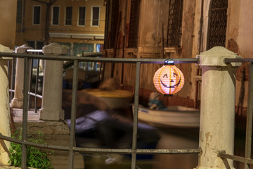 Toy Jack-o-lantern hanging on a fence near by a beautiful water channel in Venice Italy  Fototapete