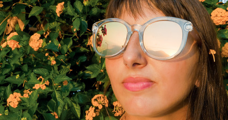 Beautiful woman in sunglasses turning to the sun