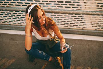 Young woman listening to music via headphones and smartphone outdoor