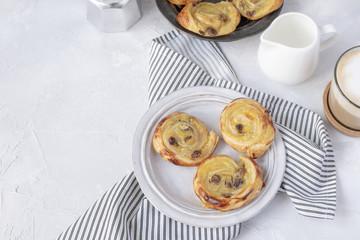 French breakfast - pain aux raisins, cappuccino, milk pitcher, coffe maker. Flat lay.