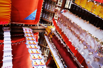 buddhist flags and textile hanging from the roof of a monastery