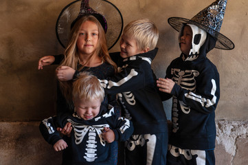 Cute children in carnival costumes, boys with girl in the garage. Black suit with the image of skeletons. Classic Halloween costume. Happy childhood of children