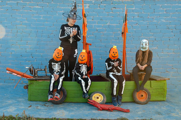 cute family in skeleton costumes for Halloween celebrations are playing pirates on wooden sailing ship. Boys, girl and mother are happy together. Masks pumpkin and dead man.