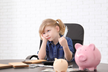 Cute little girl with money and piggy banks at table indoors